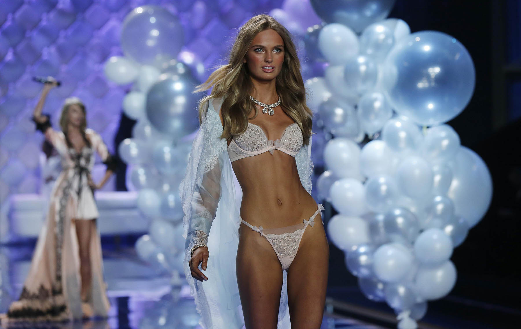 A model presents a creation as singer Swift performs during the 2014 Victoria's Secret Fashion Show in London